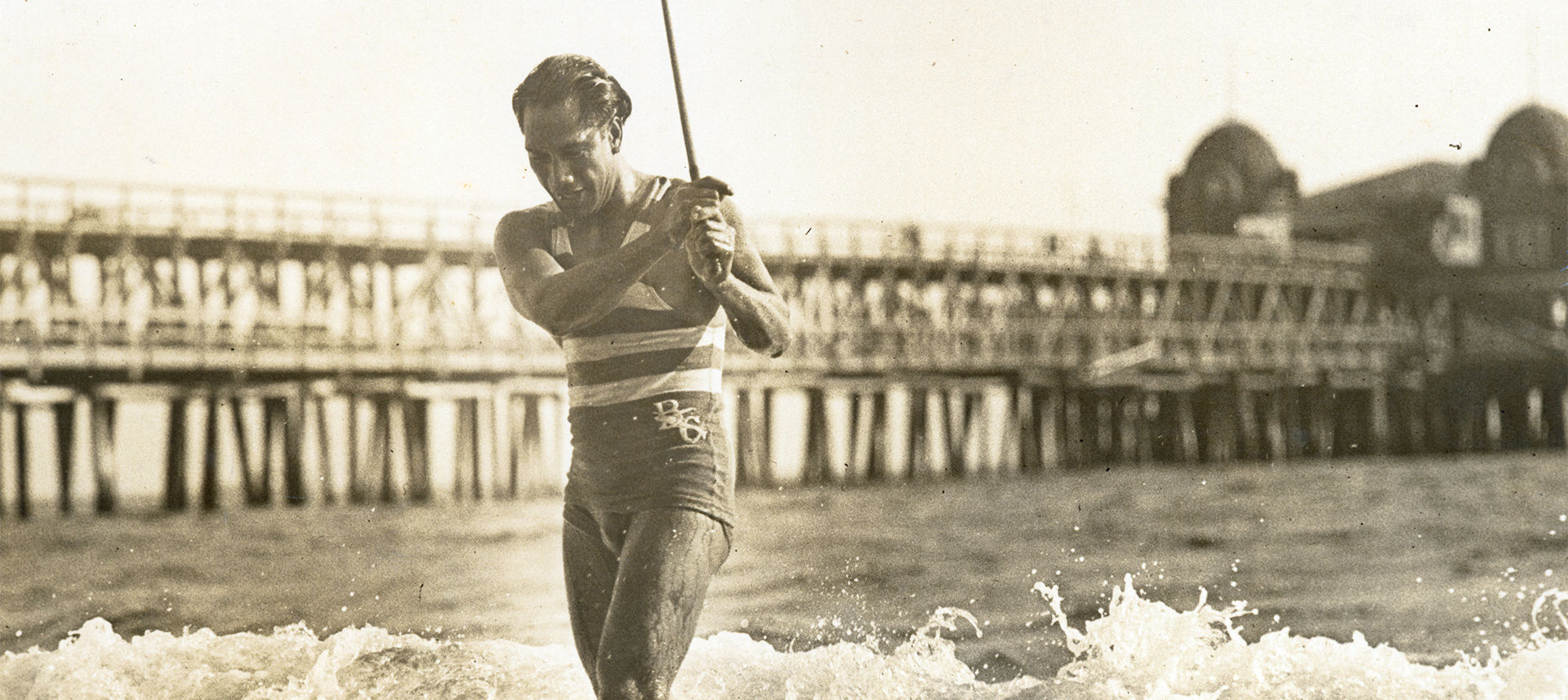 Duke exiting the water with stick in his hand in front of pier