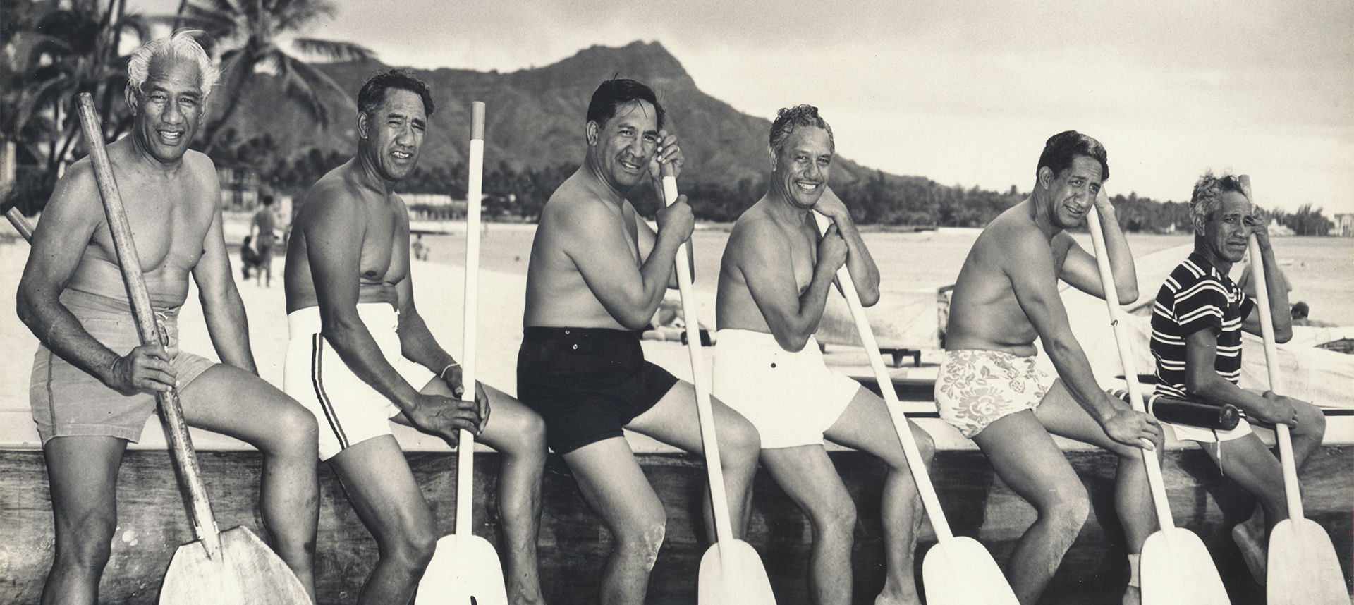 Duke and men sitting on dock with oars