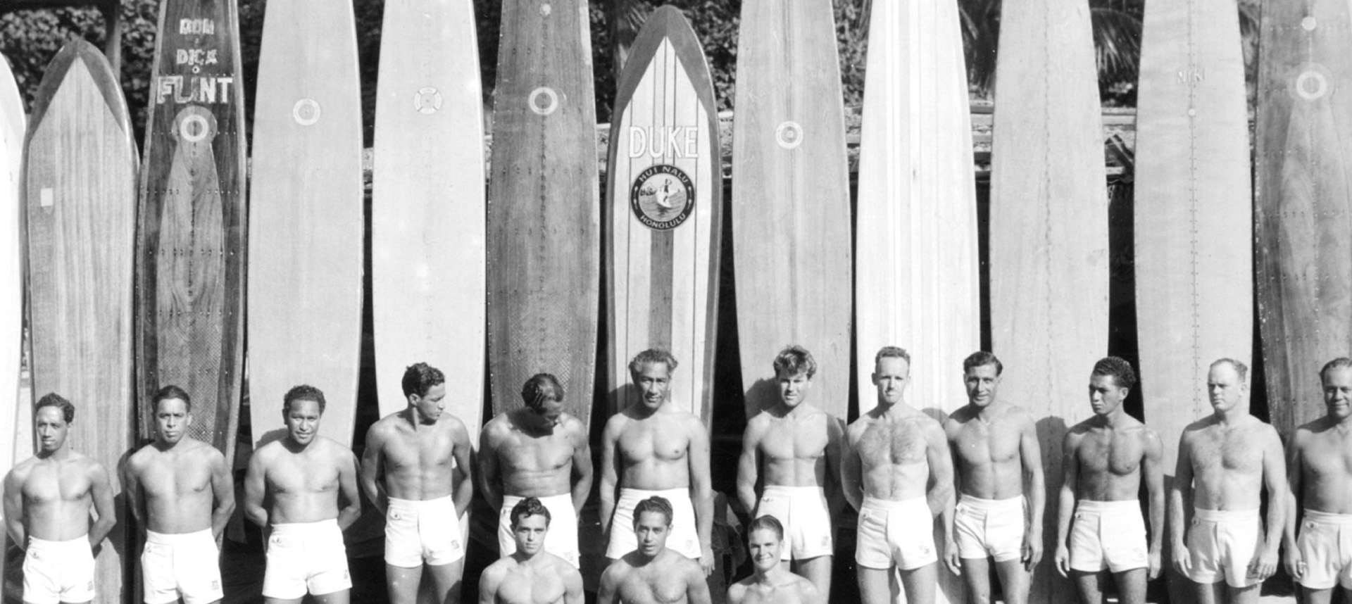 Duke Kahanamoku and the beach boys standing in front of longboards