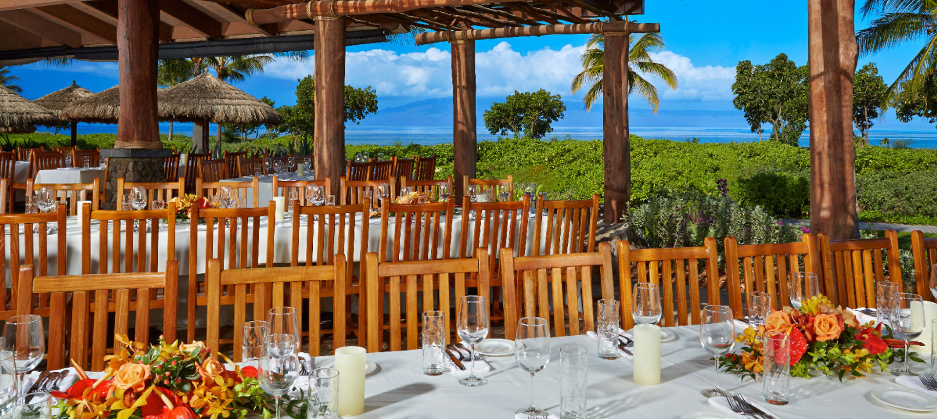 Large dining area with multiple tables in front of the ocean
