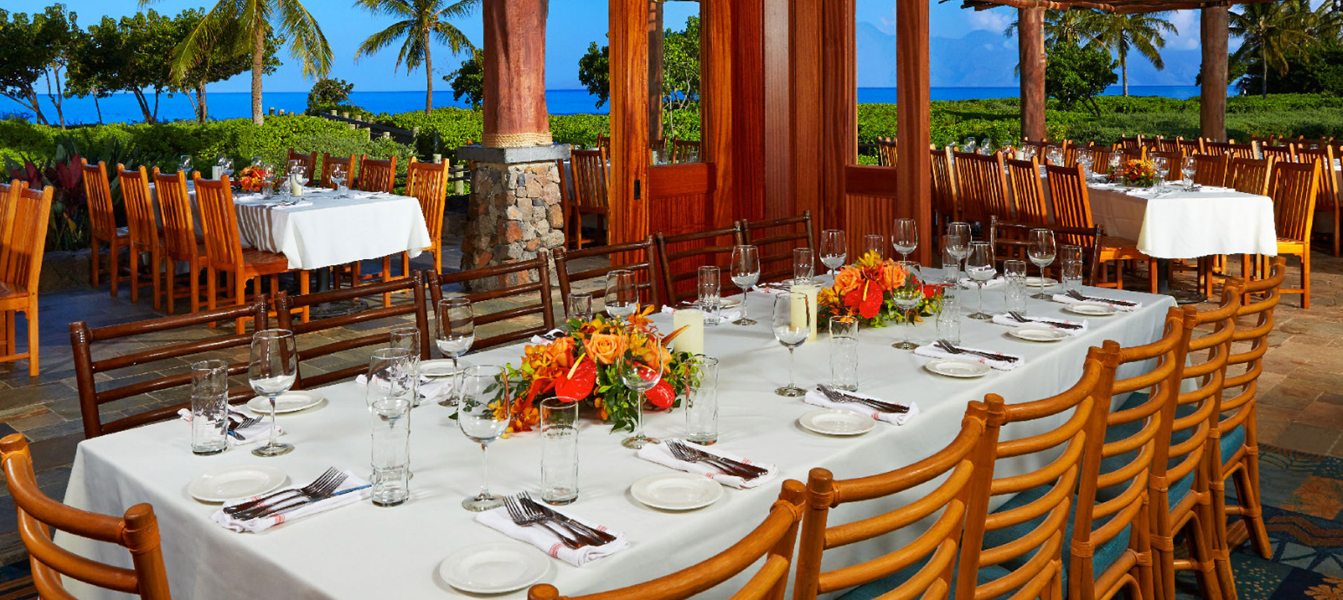 Three large dining tables set with and ocean view
