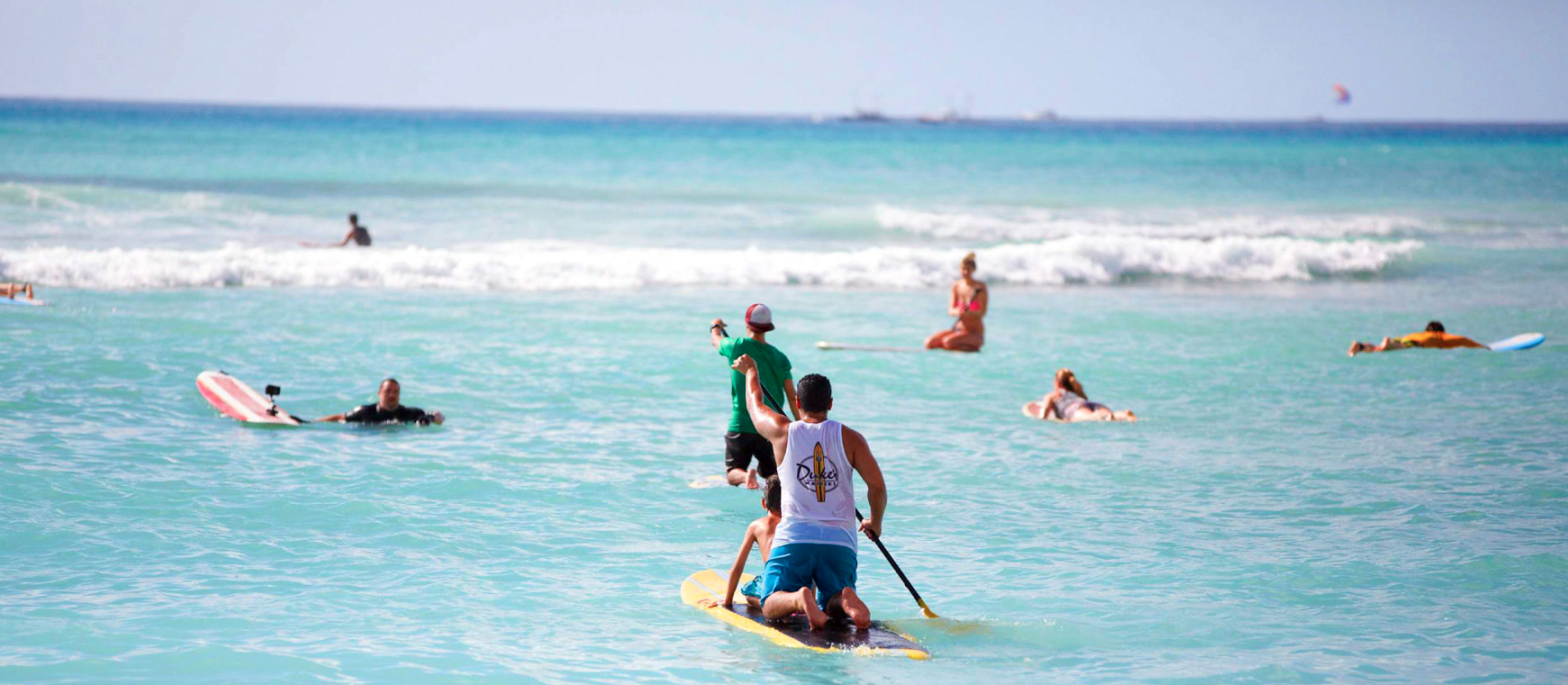 People in the ocean surfing and paddle boarding