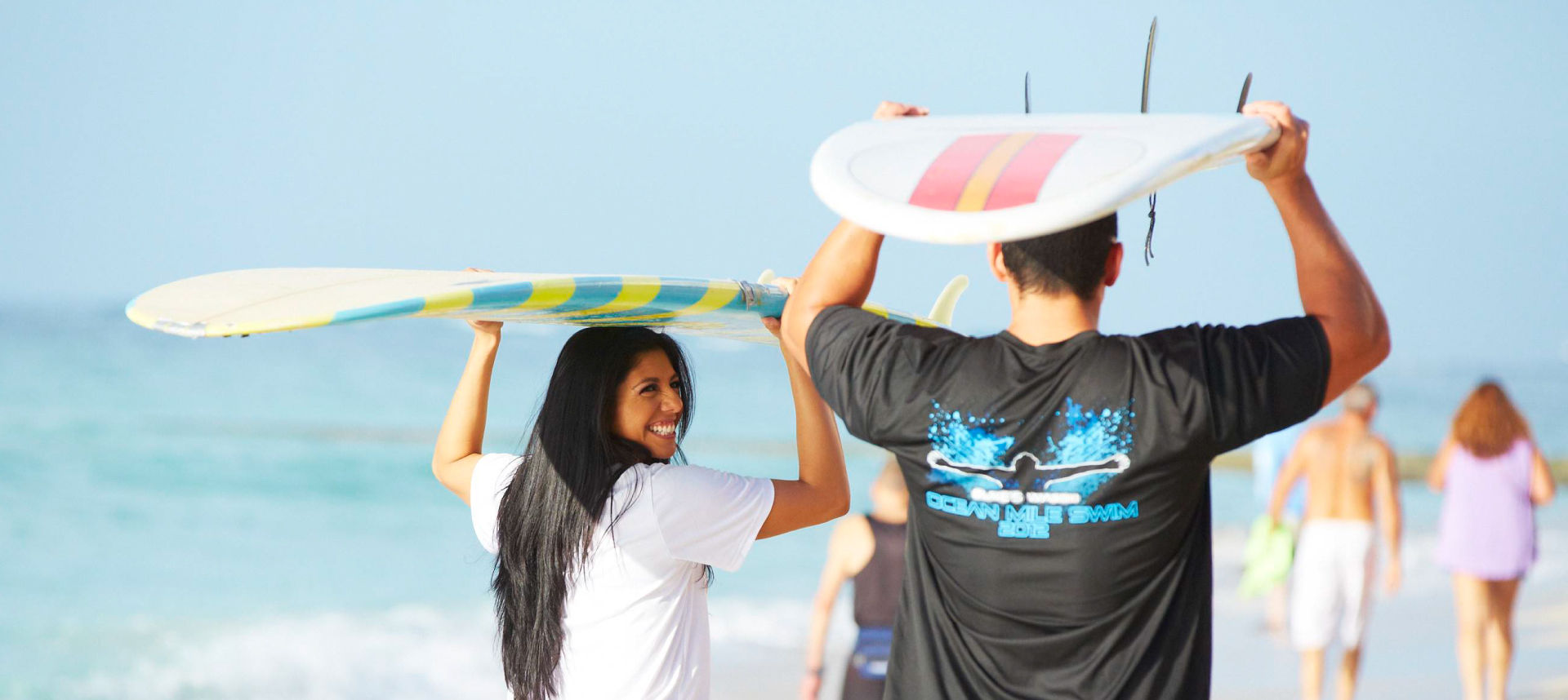 Male and female holding surfboards above their heads at the beach