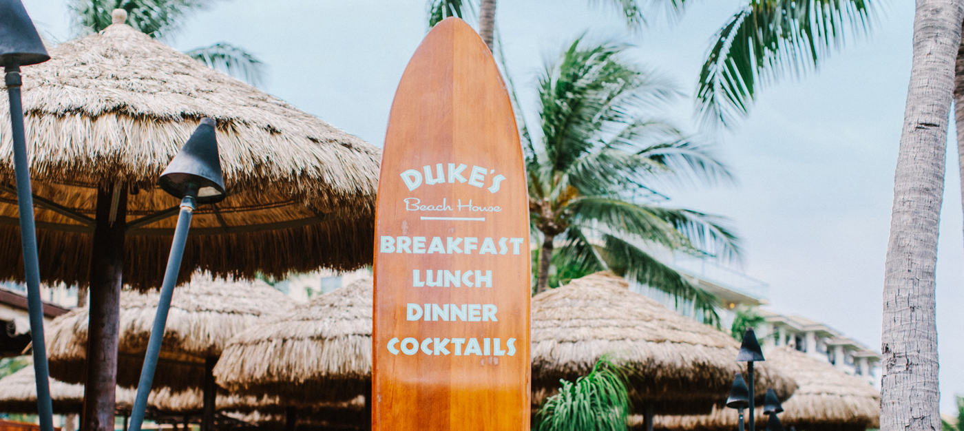 Surfboard menu with main course names in tropical area with cabanas