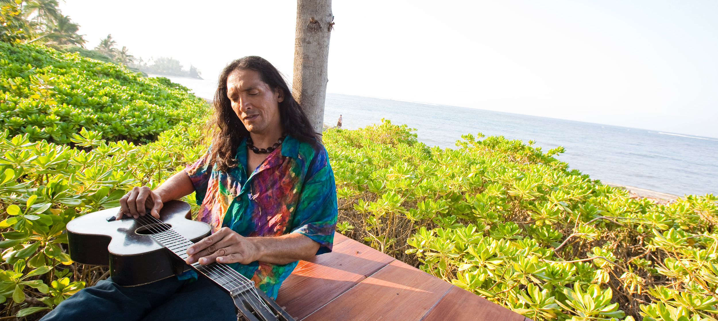 Man sitting with guitar facing flat up on lap playing by the ocean