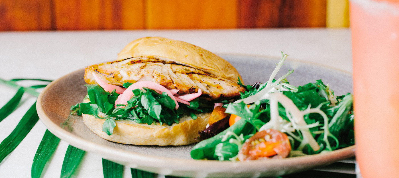 Salmon burger with pickled onions and a side salad
