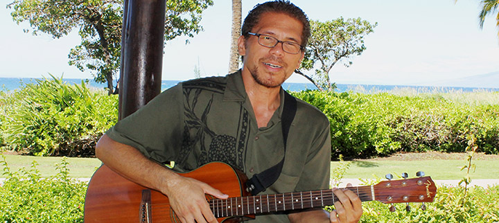 Keali'i Lum with guitar in front of sunny beach park